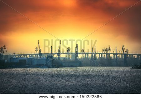 Sunset over the sea and bridge with industrial cranes