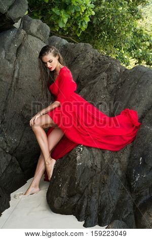 Beautiful brunette glamour woman in red dress with wet hair leaning against the rock