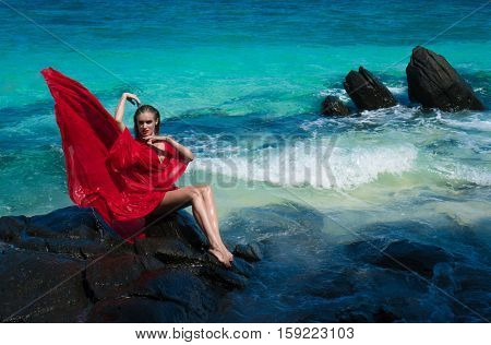 Beautiful sensual glamour woman in flying red dress with wet hair looking at the camera while sitting on the rock over beautiful lagoon sea and tropical island background