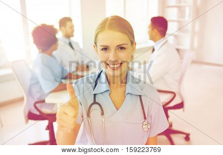 health care, gesture, profession, people and medicine concept - happy female doctor or nurse over group of medics meeting at hospital showing thumbs up gesture