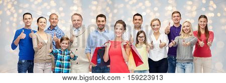 sale, family, generation and people concept - group of happy men and women with shopping bags showing thumbs up over holidays lights background