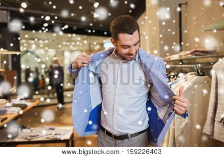 sale, shopping, fashion, style and people concept - elegant young man choosing and trying jacket on in mall or clothing store over snow