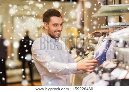 sale, shopping, fashion, style and people concept - happy young man in shirt choosing clothes in mall or clothing store over snow