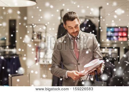 sale, shopping, fashion, style and people concept - elegant young man in suit choosing shirt in mall or clothing store over snow