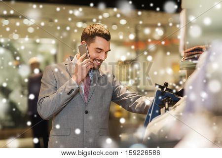 sale, shopping, fashion, communication and people concept - happy young man calling on smartphone and choosing clothes at clothing store over snow