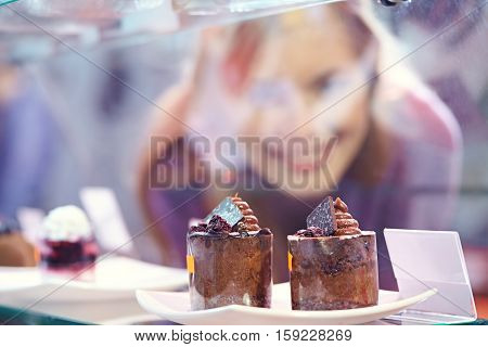 Woman looking at two chocolate cakes in shop window