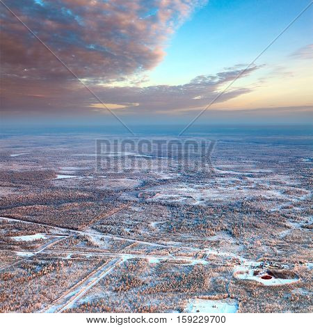 Aerial view of forest plain during a winter day. It is a top view of the oil field which is located in forested area.