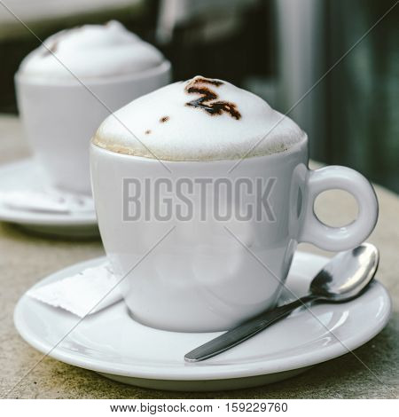 Two Cups Of Cappuccino At An Outdoor Cafe