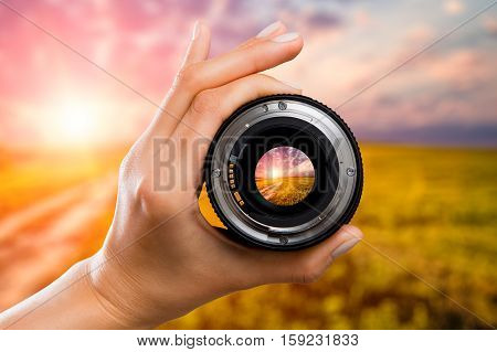 photography view camera photographer lens lense through field sunrise sunset sun sky cloud video photo digital glass hand blurred focus people concept - stock image
