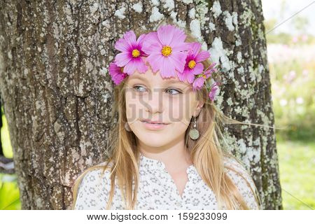 Blond young girl with purple flowers on head