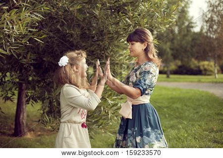 Teen girl plays with mom's hands in the summer on the nature relax on weekends holidays entertainment