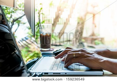 Asian man hands typing on laptop computer with blurred coffee glass and view outside window.