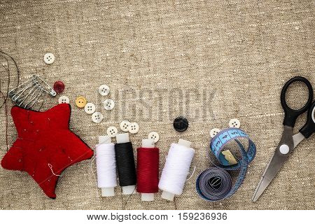 pin cushion with needlesthread and buttons for sewing