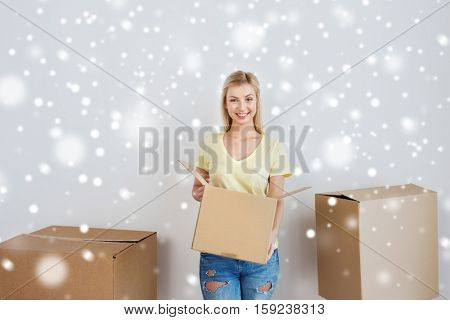 moving, delivery, housing, accommodation and people concept - smiling young woman with cardboard box at home over snow