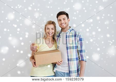 home, people, delivery, and real estate concept - smiling couple with big cardboard boxes moving to new place over snow
