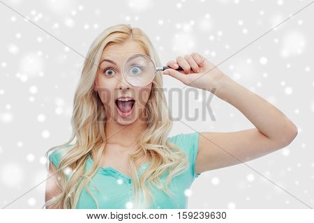 vision, exploration, investigation, education and people concept - happy young woman or teenage girl looking through magnifying glass over snow