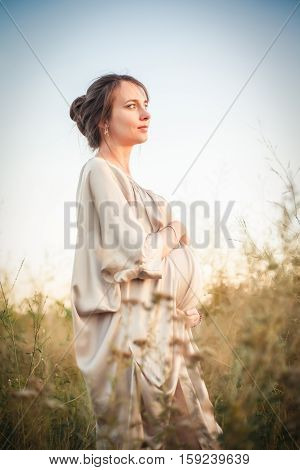Portrait of a pregnant woman in the sunset light on the nature of the field
