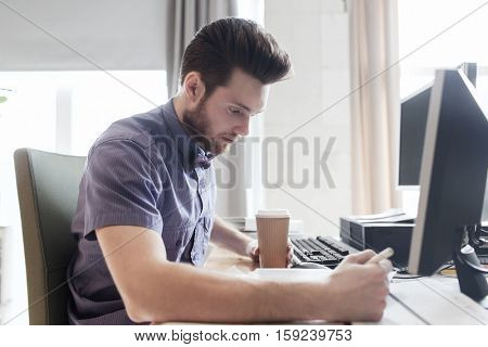 business, startup and people concept - businessman or creative male office worker drinking coffee and writing