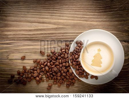 coffee cup with drawing christmas tree and coffee beans on wooden background flat lay