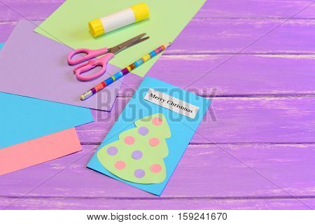 How to create simple Christmas card crafts for kids. Tutorial. Colored paper pieces, scissors, pencil, glue stick, greeting card Merry Christmas on lilac wooden background. Holiday children activity