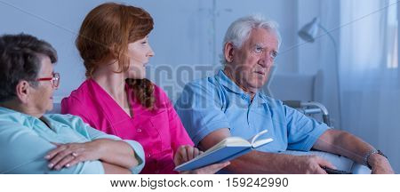 Woman Reading To Elder People