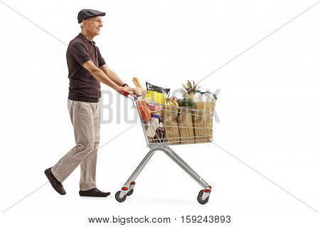 Full length profile shot of an elderly man pushing a shopping cart filled with groceries isolated on white background