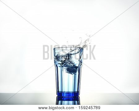 Splash of water with ice in a glassSplash of water with ice in a glass isolated on white