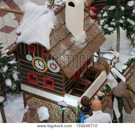 BRNO,CZECH REPUBLIC-NOVEMBER 19,2016: Family watching wooden house with elfs in shopping center Olympia on November 19, 2016 Brno Czech Republic