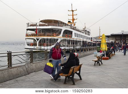 Istanbul Turkey - February 21 2013: People watching Istanbul on the Eminonu ferry pier. Istanbul Sea of Marmara the Golden Horn Galata Tower and Cityscape.