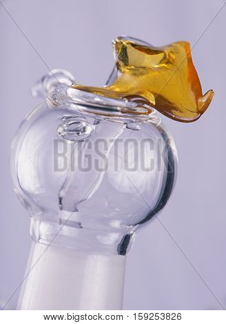 Close up view of a piece of cannabis oil concentrate aka shatter with glass rig bowl and nail isolated on white