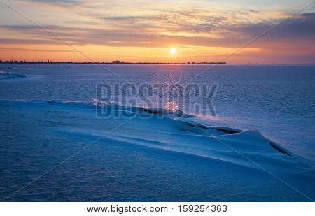 Beautiful winter landscape with lake cracks and sunset sky. Composition of nature.