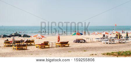 Arambol Goa India - December 08 2014: Tourists relax on the huge sandy beach of Arambol with sunbeds and sun umbrellas parasol on the Arabian Sea North Goa India