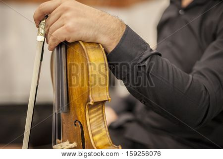 Violin player resting with bow on hand during wedding ceremony