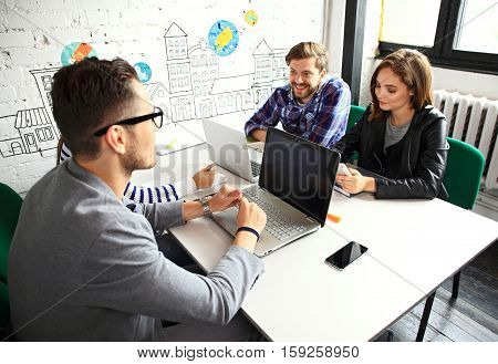 Team job. Photo young businessmans crew working with new startup project in modern loft. Generic design notebook on wood table. Horizontal, film effect