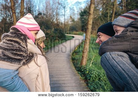 Back view of smiling parents giving piggyback ride to happy children over a wooden pathway into the forest