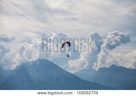 Color image of a paraglider flying with clouds in the background.