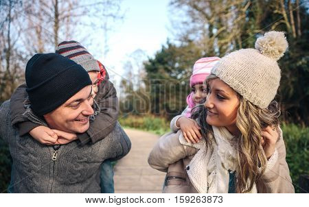 Portrait of smiling parents giving piggyback ride to happy children over a wooden pathway into the forest