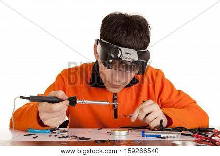 A young man learning to solder wire. Studio shot. Isolated on white background.