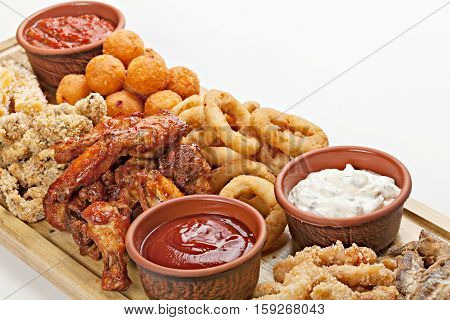 Dish of appetizers to beer. BBQ wings fried squid rings grilled cheese and several different sauces. Studio shot. Top view.