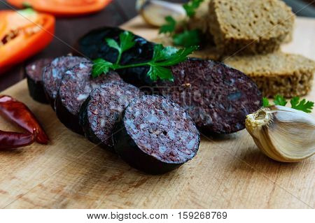 Morcillo (Spanish black pudding blood sausage) cutting slices black rye bread in a heart shape pepper garlic on a wooden board. Close up. A festive meal on Christmas Easter