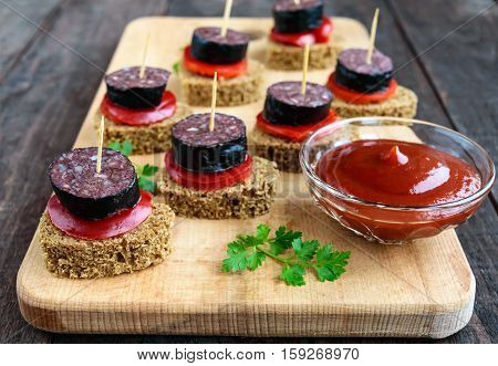 Sandwiches with black rye bread in the shape of a heart blood sausage (Morcillo) and pieces of sweet pepper on skewers tomato sauce on a dark wooden background. Close up