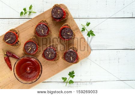 Sandwiches with black rye bread in the shape of a heart blood sausage (Morcillo) and pieces of sweet pepper on skewers and tomato sauce on a white wooden background. The top view