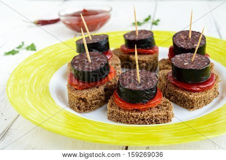 Sandwiches with black rye bread in the shape of a heart blood sausage (Morcillo) and pieces of sweet pepper on skewers and tomato sauce on a white wooden background. Close up