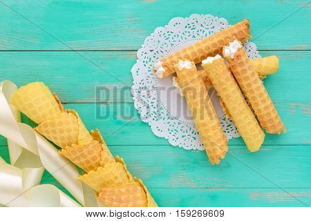 Tender honey wafers in the form of tubes stuffed with air cream on white lace napkin. The top view