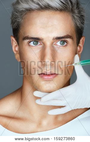 Young man gets beauty facial injections in the nasolabial folds. Professional cosmetician making rejuvenate injection. Beauty concept