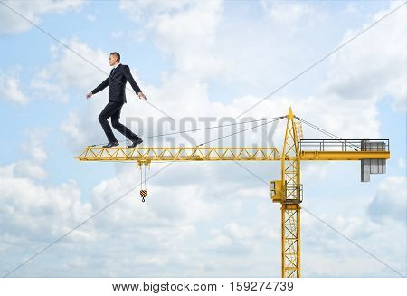 A businessman walking on the yellow construction crane, trying to balance himself and get to the end of the jib, on the sky background. Business difficulties and risks. Overcoming obstacles. Construction equipment and machinery. House-building and reconst