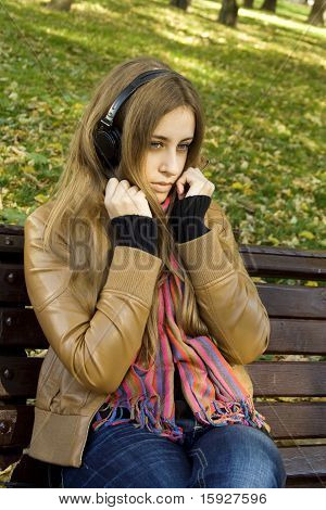 Attractive girl in park listens to music