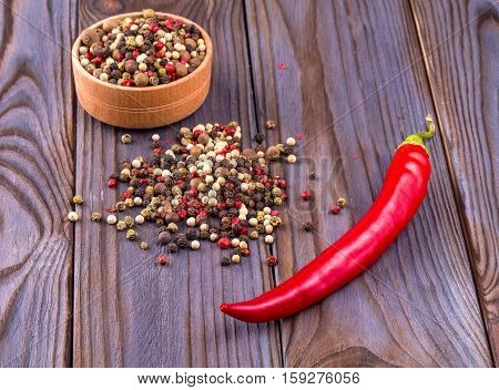 Red hot chili peppers on wooden backround with wooden cup and round black pepper