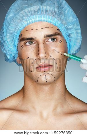 Beautiful young man gets beauty facial injection in eye area. Photo of young man with plastic surgery guideline marks on his face. Cosmetology concept