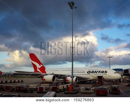 Sydney, Australia - Dec 22, 2015: A Qantas Airbus A380 wide-body airplane docked to the jetway at Sydney's Kingsford-Smith International Airport. Ground crew are busy preparing the plane. Qantas is the flagship carrier airline of Australia.